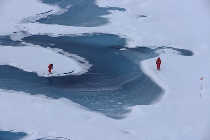 AWI-Meereisphysiker untersuchen Schmelztümpel auf dem arktischen Meereis.  Foto von der Polarstern-Expedition ARK 26-3.   AWI sea-ice physicists investigate melt ponds on Arctic sea ice. This photo was made during the Polarstern expedition ARK 26-3.