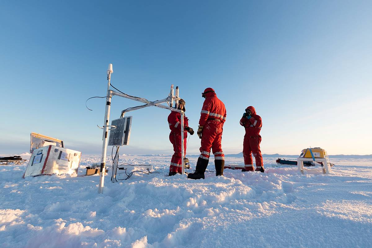 Group of researchers at work on the ice, anchoring of the buoys, for determining of sea ice thickness (center) and the snow thickness (Yellow box, right).